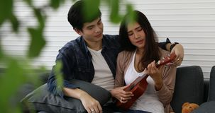 Asian man teaching his girlfriend. Young good looking Asian man teaching his good looking Asian girlfriend how to play Ukulele on dark grey sofa in their home stock video
