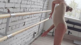 Attractive blonde in leotard practices dance movements on barre with stretching. Young good-looking blonde caucasian female dressed in beige leotard is stock video footage