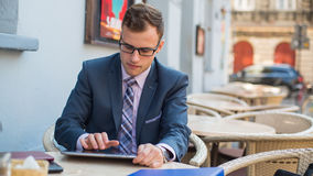Young good-looking businessman sitting at coffee table, using tablet in cafe. Stock Photos