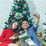Young and good looking caucasian couple sitting on sofa happy an. D smile selfie in front of big decorated christmas tree and take a selfie with smartphone stock photos
