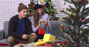 Caucasian couple wrapping gift box . stock footage
