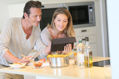 Young good looking couple preparing meal in the kitchen Royalty Free Stock Images