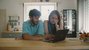 Young good-looking couple is sitting at the kitchen table looking at the computer and talking. Slow motion stock footage