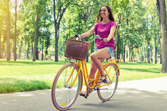 Young good-looking female enjoying her bicycle ride on the parkw Royalty Free Stock Image