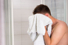 Young good-looking guy dries his face with a clean towel Royalty Free Stock Photo