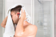 Young good-looking guy dries his wet hair with a clean towel Stock Images