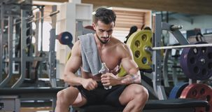 A young good looking man , looks on his phone while he s at the gym and proceeds to drink water. 4k stock video