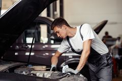 A young and good-looking mechanic is doing his job at a car service royalty free stock images
