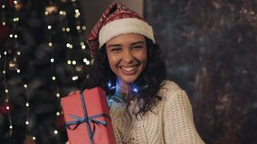 Young good looking mulatto woman at santas hat and blinding lights on her neck shaking present box. she sitting near stock video