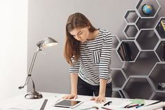 Young good-looking serious female designer student with dark hair in stylish casual outfit standing near table, looking. In digital tablet, trying to figure out stock photos