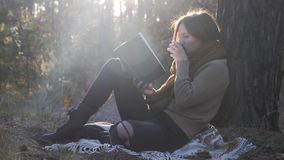 Young good-looking woman in warm cozy clothes reading book, holding cup of tea or coffee and drinking in autumn forest at sunrise.  stock video