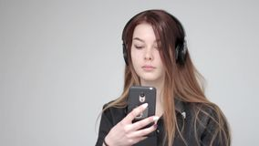 Young good looking woman wireless headphones uses tablet and phone to take photo stock video