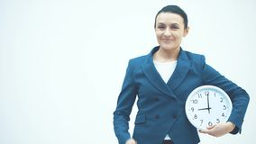 Young good teacher standing on a white background. Holds the white clock rejoices and shows for an hour. Dressed in a. Blue jacket. Close up. Copy space. Happy stock footage