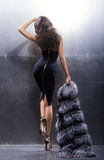 Young and gorgeous actress in a long dress. Young and gorgeous actress in a long black dress on a metal wall background Stock Photo
