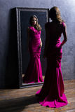 Young and gorgeous actress in a long dress. Preparing in a dressing room in front of a mirror Royalty Free Stock Images