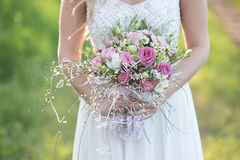 Young gorgeous bride holding a bridal bouquet. Young bride with perfect skin and green eyes Flying beautiful hair stock photo