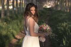 Young gorgeous bride with perfect skin and green eyes holding a bridal bouquet. Young fashion bride with perfect skin and green eyes holding a wedding bouquet royalty free stock photo
