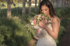 Young gorgeous bride with perfect skin and green eyes holding a bridal bouquet. Young bride with perfect skin and green eyes Flying beautiful hair royalty free stock image