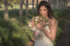 Young gorgeous bride with perfect skin and green eyes holding a bridal bouquet. Young bride with perfect skin and green eyes Flying beautiful hair stock photography