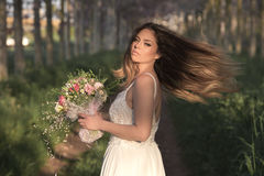 Young gorgeous bride with perfect skin and green eyes holding a bridal bouquet. Young bride with perfect skin and green eyes .Flying beautiful hair stock photography