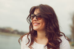 Young gorgeous brunette woman wearing sunglasses. Outdoor fashion closeup portrait of young gorgeous brunette woman wearing sunglasses in summer sunny day Royalty Free Stock Photography