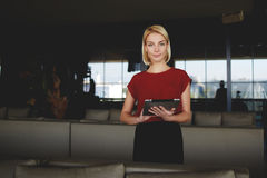 Young gorgeous businesswoman holding in hands digital tablet while standing in modern restaurant interior, Royalty Free Stock Photo