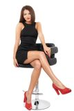 Young gorgeous caucasian brunette in black dress on the chair Stock Images