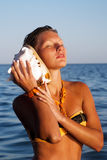 Young gorgeous female listening seashell song Royalty Free Stock Photo