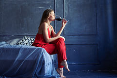 Young gorgeous girl drinking red wine while sitting on the bed Royalty Free Stock Photos
