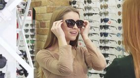 Happy young beautiful woman trying on sunglasses at the optics store stock footage