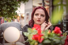 Young gorgeous redheaded woman sitting in an outdoor cafe dressed in retro fashion clothes. royalty free stock photography
