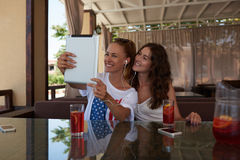 Young gorgeous smiling ladies making self portrait with digital tablet camera during brunch in cozy coffee shop, Stock Images