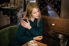 Young gorgeous thoughtful female drinking tea or coffee in coffee shop while enjoying her leisure time alone, nice business woman stock image