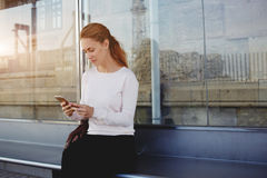 Young gorgeous woman concentrated reading information in Internet via cell telephone while waiting for a taxi on a bus stop, Stock Image