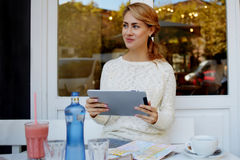 Young gorgeous woman dreaming about something while sitting with portable touch pad in cozy sidewalk cafe, Royalty Free Stock Photos