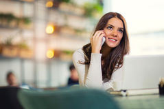 Young gorgeous woman having smart phone conversation. While sitting in front of open laptop computer in cafe bar Royalty Free Stock Photos