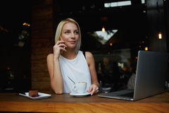 Young gorgeous woman having smart phone conversation while sitting in front of open laptop computer in cafe bar Stock Images