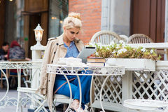 Young gorgeous woman reading electronic book on touch pad while sitting in coffee shop in the fresh air. Beautiful blonde female working on her digital tablet Stock Image