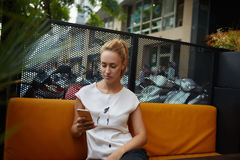 Young gorgeous woman reading text message on her mobile phone while sitting alone in cafe bar outdoors, Stock Photo