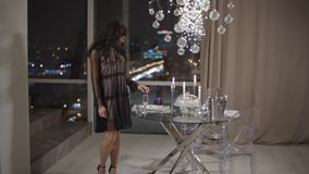 Young woman standing near window with a spectacular view of a night city. Young gorgeous woman standing near a window with a spectacular view of a night city stock video