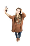 Young gorgeous woman taking self portrait or selfie with smartphone Royalty Free Stock Photography