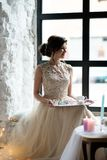 Young gorgeous woman wearing sleeveless evening dress. She is waiting for her boyfriend sitting in front of window with tray of sweets and coffee Stock Image