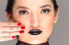 Young gothic beautiful woman with red nails. Young gothic beautiful woman with black makeup and red nails royalty free stock photo