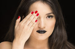 Young gothic beautiful woman with red nails. Young gothic beautiful woman with black makeup and red nails covering one eye stock photography