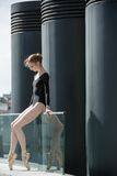 Young graceful ballerina in black bathing suit on Stock Photography