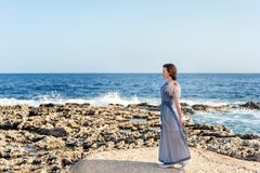 A young graceful maid treads lightly along the shore from the lava and brightly the blue sea and sky. Young graceful maid treads lightly along the shore from the stock image
