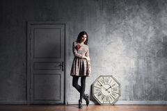 Young and graceful woman posing in an ancient interior. With a vintage clock Stock Images