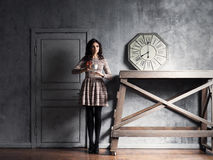 Young and graceful woman posing in an ancient interior. Young and graceful woman posing in ancient interior with a vintage clock Royalty Free Stock Image