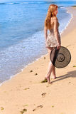 Young graceful woman  with straw hat in hands Stock Photo