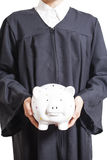 Young graduate in  gown holding  piggy bank Stock Photo